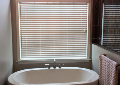 arched bathroom window with 2 in wood blinds