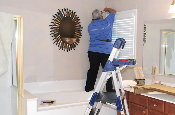 Charles installing valance in bathroom